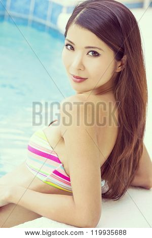 Instagram filter style photo of beautiful and sexy young chinese asian woman wearing a bikini leaning on side of a turquoise blue swimming pool. Spa, healthy living and health club concept.