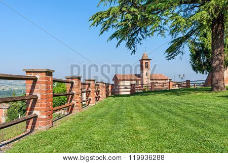 Brick fence along green lawn as small parish church on background under blue sky in Piedmont, Northern Italy.
