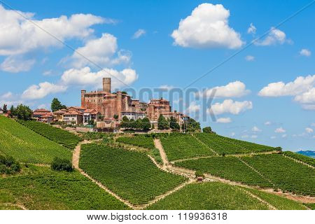 Small town with medieval castle among green vineyards under blue sky in Piedmont, Northern Italy.