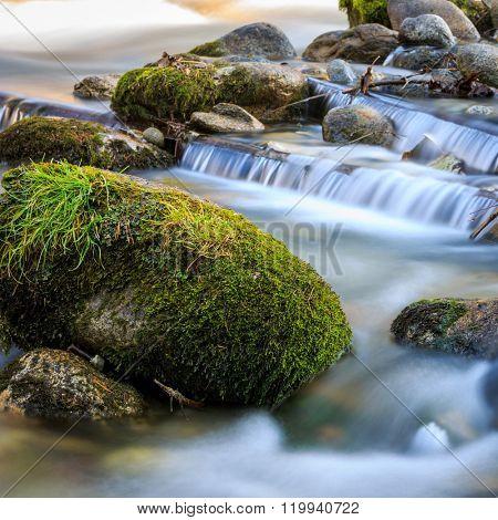 Green stone in water of small waterfall on mountain brook