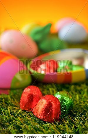 closeup of some chocolates wrapped in foil of different colors, an egg-shaped box, a green easter rabbit and some ornamented eggs on the grass