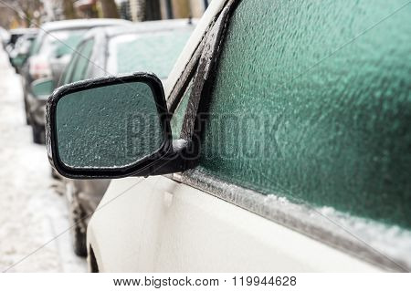 Car mirror and windows are covered with ice after freezing rain.