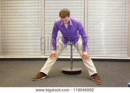 man stretching legs and back sitting on pneumatic stool in his office