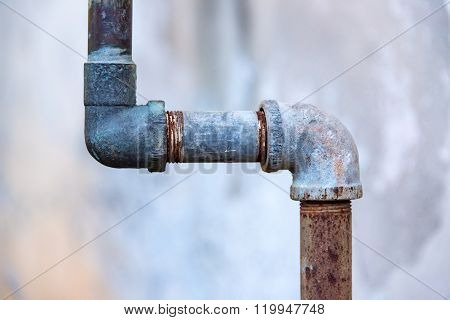 Rusty old faucets and piping system in backyard
