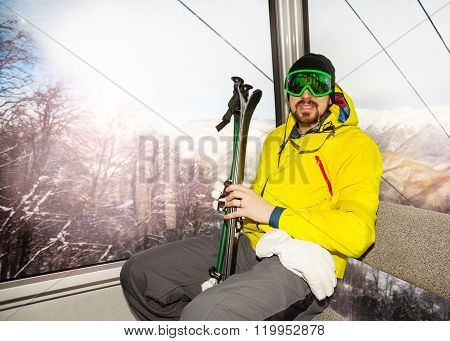 Man skier sit in ski lift cable car cabin