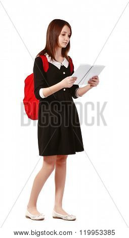 Beautiful schoolgirl with schoolbag reading book isolated on white