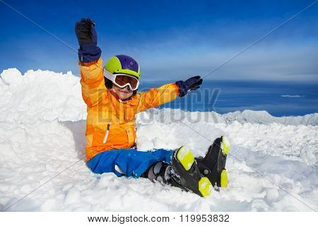 Happy skier boy sit with lifted hands in snow