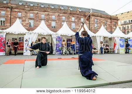 STRASBOURG FRANCE - APRIL 24 2015: Samurai sword public demonstration by two men wearing traditioanl samurai Hakama in Place Kleber Strasbourg Alsace Eurometropole