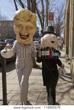 Asheville, North Carolina, USA - February 2, 2016: Humorous effigies of Hillary Clinton and Mr. Monopoly hold hands and carrying bags of money as they skip down the street followed by a marching Bernie Sanders supporters