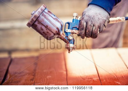 Close-up Of Spray Gun Getting Paint Over Timber. Young Painter Renovating