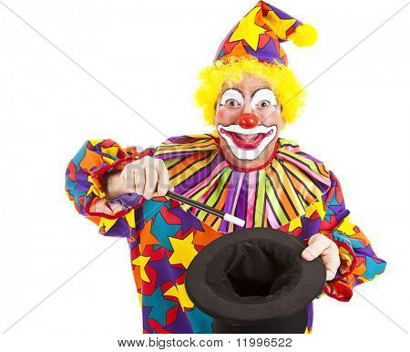 Cheerful birthday clown does a magic trick with a want and top hat.  Isolated on white.
