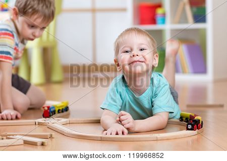 Children boys playing rail road toy in nursery