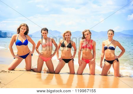 Cheerleaders In Bikinis Stand On Knees In Line On Wet Sand