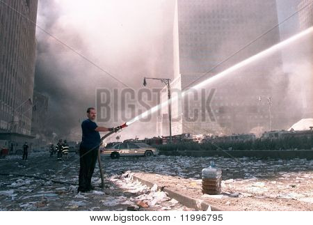 NEW YORK - SEPTEMBER 11:  An unidentified civilian uses a fire hose as he works near the area known as Ground Zero after the collapse of the Twin Towers September 11, 2001 in New York City.