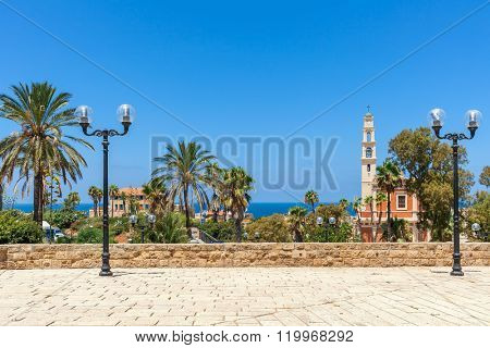 Saint Peter's church among palms under blue sky as seen from view point with lampposts in Jaffa, Israel.