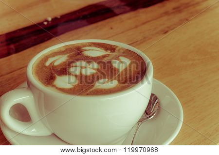 Hot coffee with flower from milk foam on wooden table vintage retro style