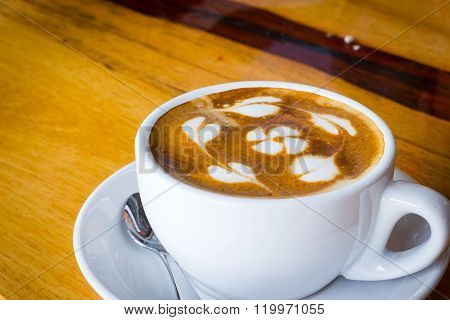 Hot coffee with flower from milk foam on wooden table