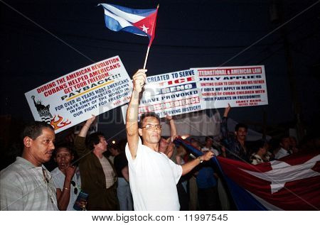 LITTLE HAVANA, FL - APRIL 14: Protesters hold signs near the family home of Elian Gonzalez on April 14, 2000 in Little Havana, Florida. Elian was forcibly taken into custody on April 22.