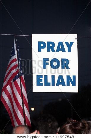 "LITTLE HAVANA, FL - APRIL 14: A ""Pray For Elian"" sign hangs near the family home of Elian Gonzalez on April 14, 2000 in Little Havana, Florida. Elian was forcibly taken into custody on April 22."