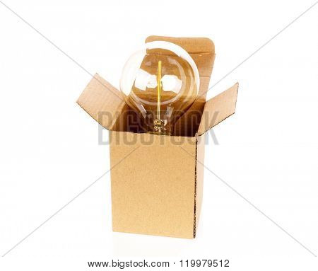 Glowing light bulb over open cardboard box