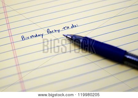 Closeup of birthday party to do list on paper with blue pen written writing