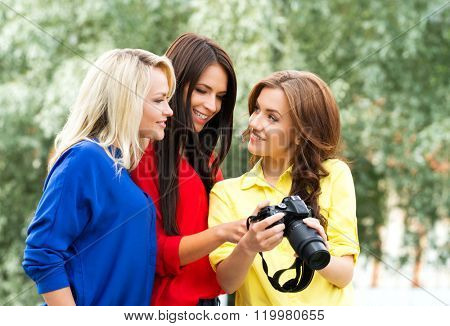 Three young sexy female photographers watching photos on a new slr camera.