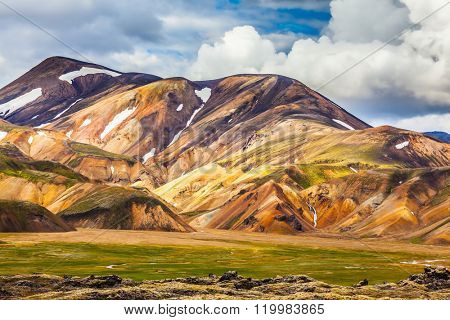 Summer volcanic tundra.  Bright, multi-colored rhyolite mountains - yellow, orange, green and blue. Travel to Iceland in July