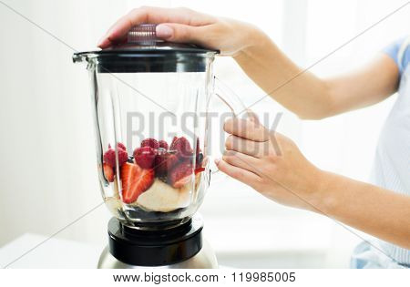 healthy eating, cooking, vegetarian food, dieting and people concept -close up of woman with blender making fruit shake r at home