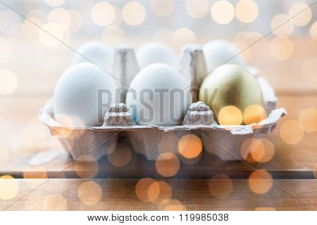 easter, food, cooking and object concept - close up of white and golden eggs in egg box or carton wooden surface over holidays lights