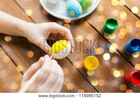 easter, holidays, tradition and people concept - close up of woman hands coloring easter eggs with colors and brush over holidays lights