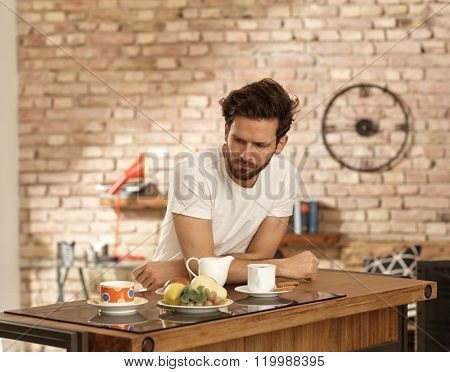 Sleepy young man elbowing on breakfast table in the morning.