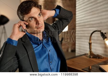 Businessman talking on mobilephone, looking away.