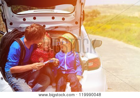 father with two kids looking at map while travel by car
