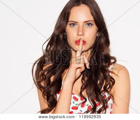 Portrait of beautiful young woman pointing finger to her lips over white background. Concept silent