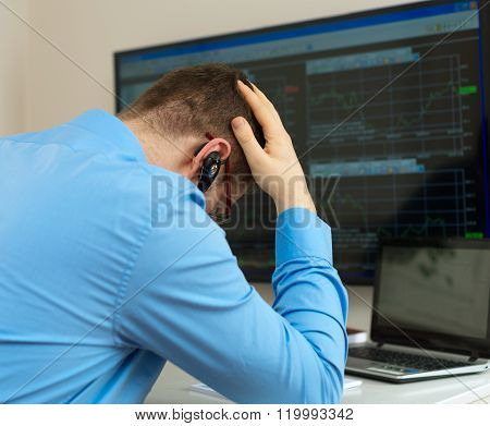 Upset stock trader in front of computer.