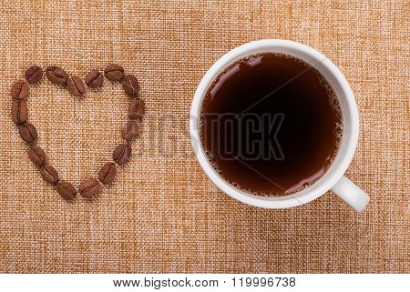 Cup Of Coffee And Grains Laid Out In A Heart Shape On The Tablecloth. View From Above .