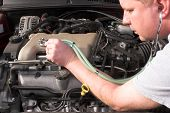 picture of mechanical engineering  - an auto mechanic working on a car engine - JPG