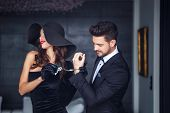 Sexy Woman In Hat Holding Young Rich Lover On Handcuffs Indoor poster