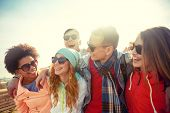 tourism, travel, people, leisure and teenage concept - group of happy friends in sunglasses hugging  poster