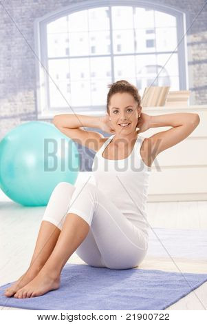 Hübsche junge Frau Übungen am Boden zu Hause, Lächeln.?