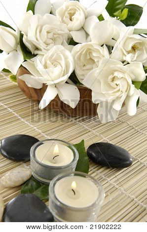 Aromatic spa set - fresh gardenia flowers in bowl with candle and zen stones