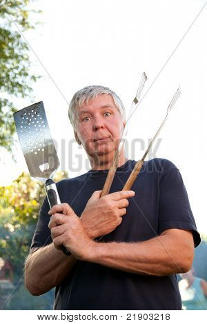 Mature man ready to cook on the BBQ.