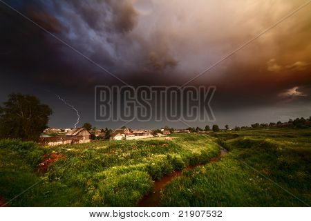 Storm rainy clouds with flash over small village