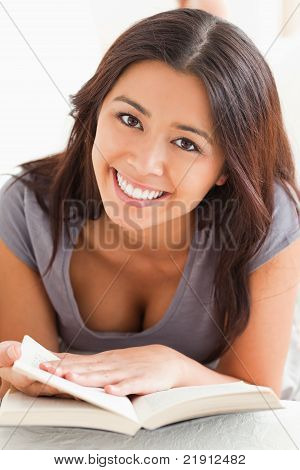 Close Up Of A Cute Woman Holding A Book In Her Hand Ans Looking Into Camera