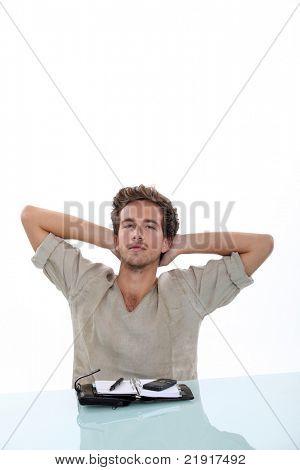 Hombre estirando sus brazos detrás de su cabeza, tomando un descanso de la agenda abierta en el escritorio