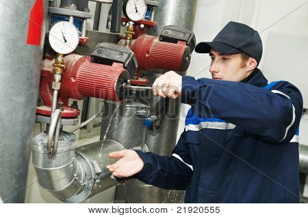 maintenance engineer repairing water pump of heating system equipment in a boiler house