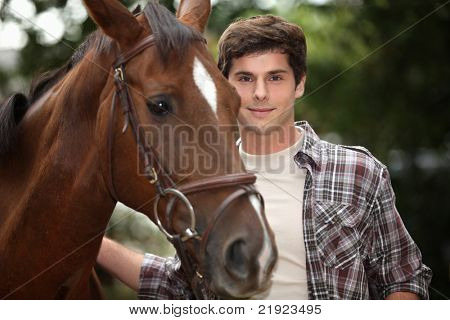 young man and a horse in the forest