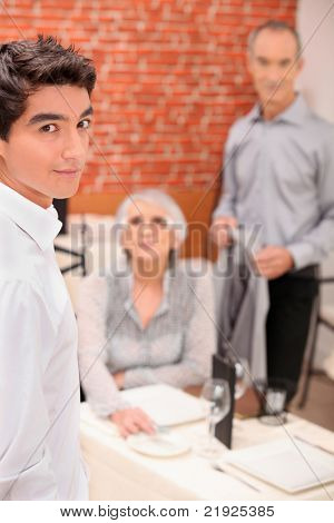 Young waiter serving an older couple in a restaurant