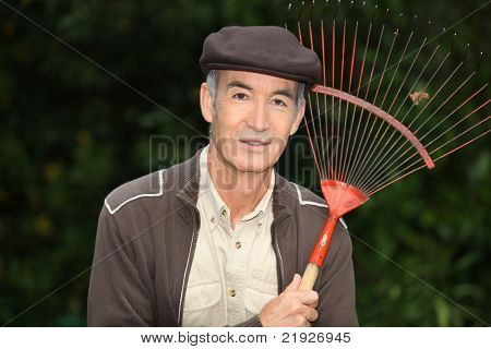 65 years old man wearing brown clothes and holding a rake