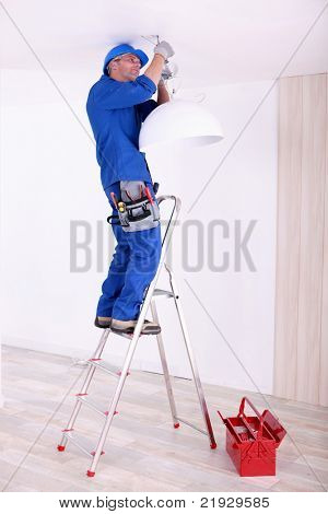 Electrician hanging a ceiling light